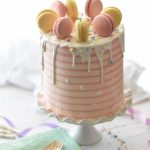 a pastel-colored macaron-topped pink cake on a cake plate.