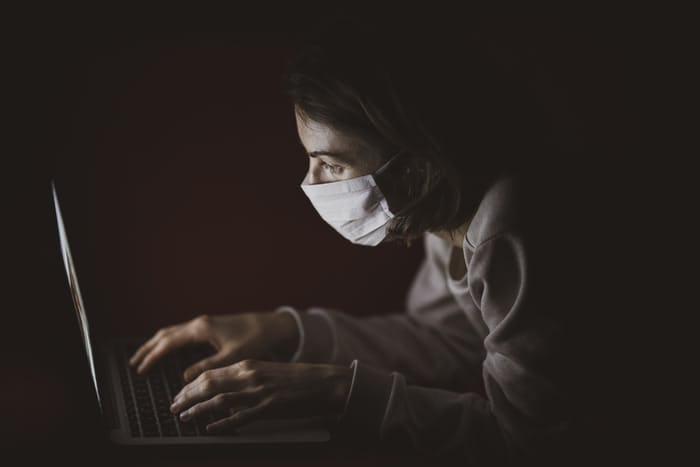 women doing copywriting on her laptop, with mask on