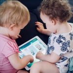 marketing to kids: two toddlers looking into an Ipad