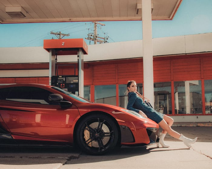 influencer marketing for a red car, model leaning on the car in front of a gas station